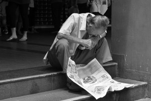 """Headlines: Engrossed in the news"" Photo by John Ragai (CC BY 2.0)"